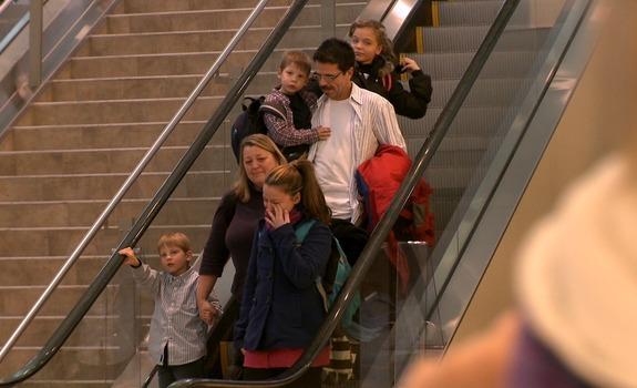 Family riding down escalator - screenshot from The Dark Matter of Love.