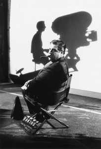 Director sitting in chair with shadow of camera on wall