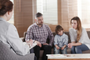 Rear view of female psychologist helping young family with a kid to solve child development problems. Family sitting on a sofa in the blurred background
