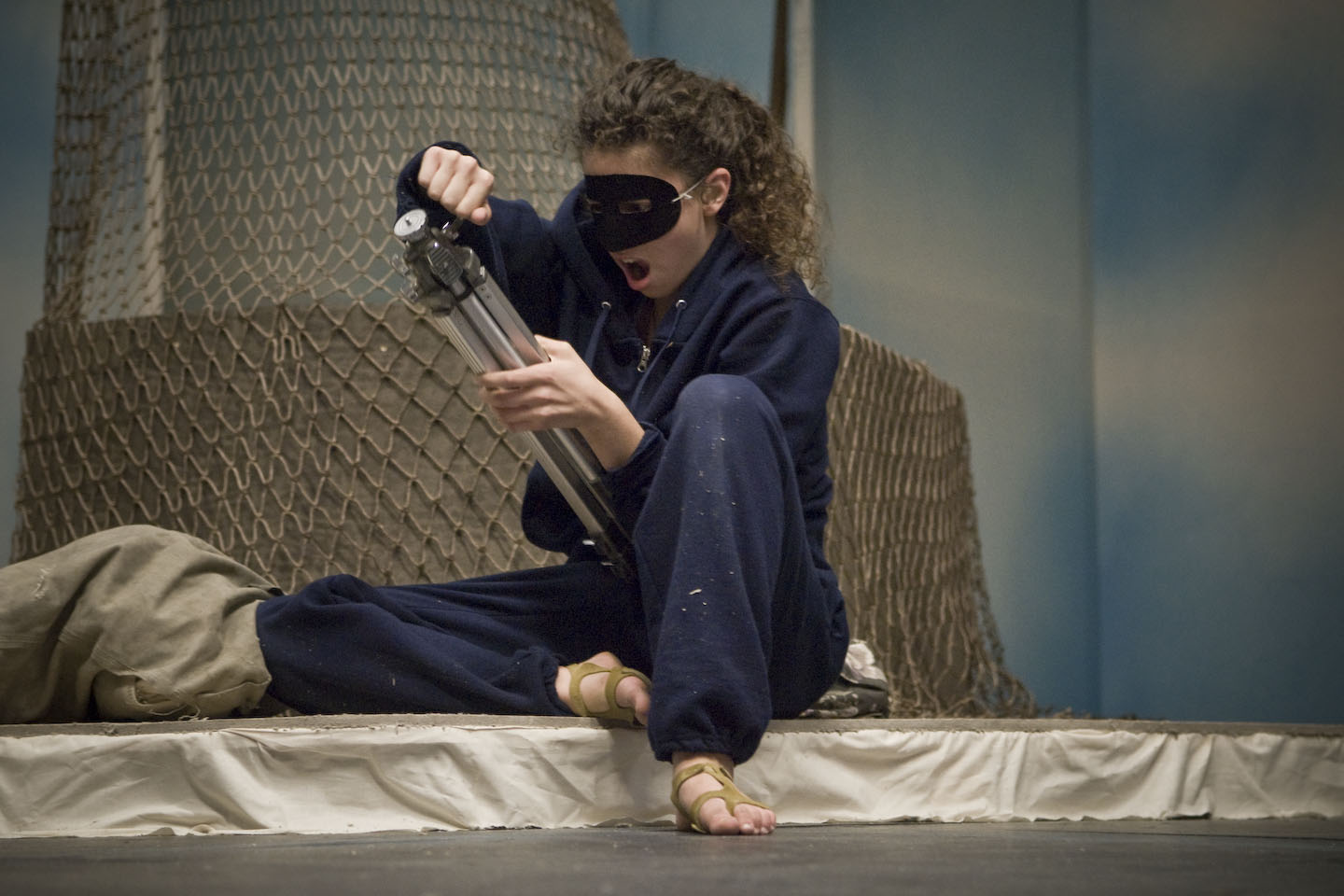 "Sara Bogomolny, in the title role of ""Betty the Yeti,"" wore a black mask during rehearsals to set herself apart from the human characters. And yet, Betty is fascinated by manmade objects—everything from tripods to video games. Photo by Peter Jennings."