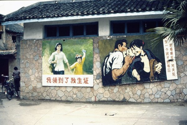 """These propaganda posters, photographed in the city of Giulin in 1984, encouraged compliance with the Chinese government's family planning policies. The daughter in the poster on the left is holding a one-child certificate—a fact announced in the caption. Parents who signed such a document became eligible for certain benefits. In the poster on the right, the caption reads, """"Respond Actively to the Call That Each Couple Should Have Only One Child."""" Photo by Katte Belletje."""