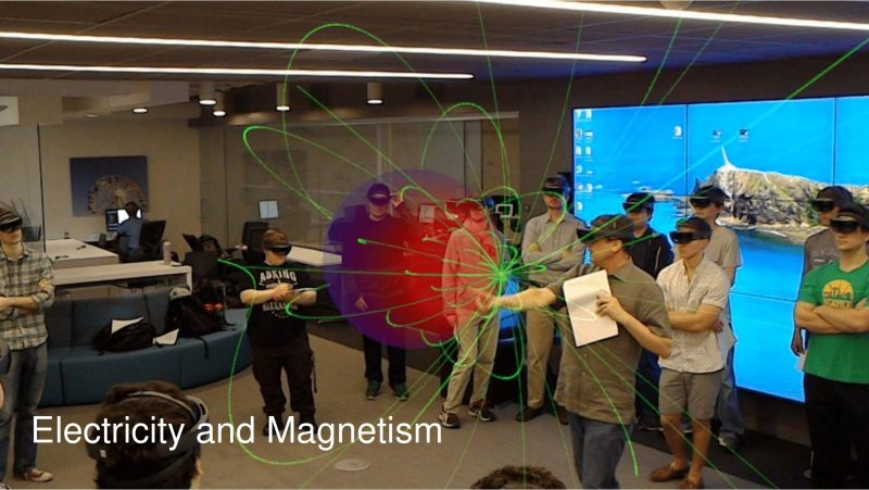 Physics comes to life for Professor Martens' 2017 electricity and magnetism class at the Interactive Commons. The class views the electric field lines in green produced by a point charge sitting outside a conducting sphere, shown in red.