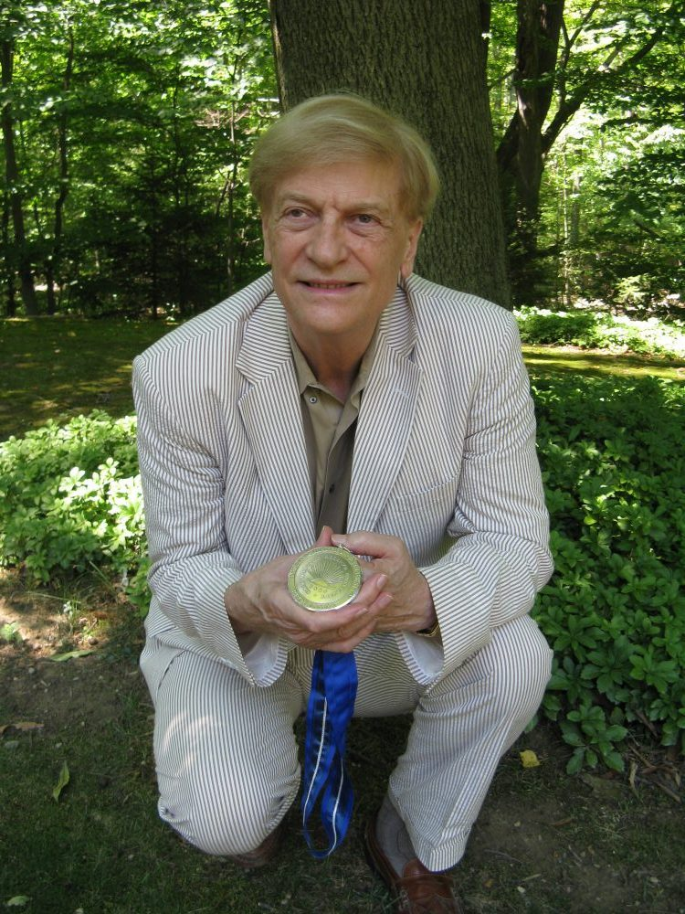 """Prof. Robert """"Doc"""" Brown, shown here in characteristic un-pretentious fashion, with his Distinguished University Professor award."""