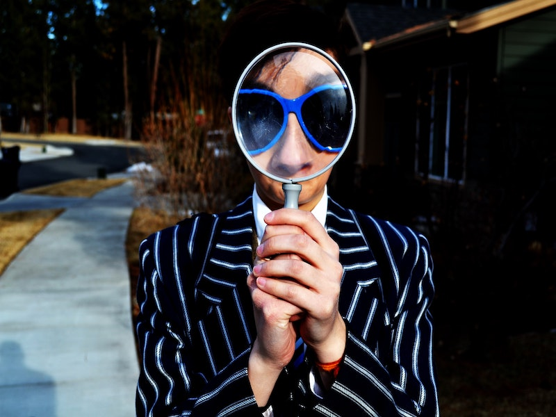 person holding magnifying glass in front of their face