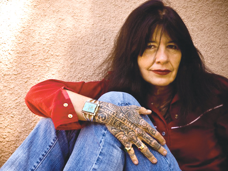 Author Joy Harjo media pic with hand accross knee.