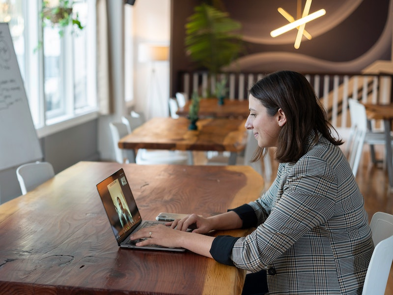 Female business executive interviews a student via zoom while sitting in trendy cafe.