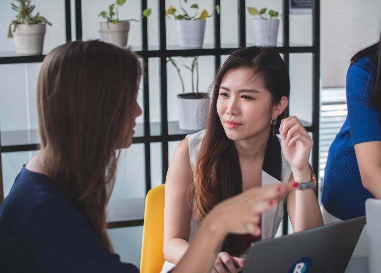 Two young women in engaged conversation at the end of a table during a large group seminar. Photograph by Mimi Thian from Unsplash