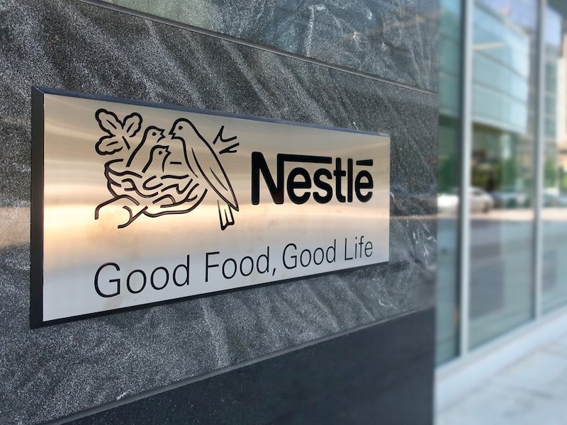 """Photograph of the entrance to offices of the Nestle Corporation, featuring their logo of birds nesting with the phrase """"Good Food. Good Life"""""""