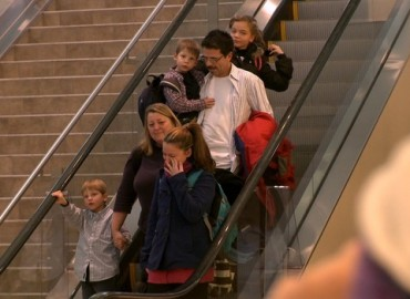 Family riding down escalator - screenshot from The Dark Matter of Love.