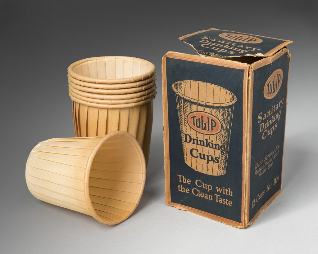 Yellowing white fluted paper drinking cups next to a blue, brown and orange box in deteriorating condition. Text reads: Tulip Drinking Cups, The Cup with the Clean Taste