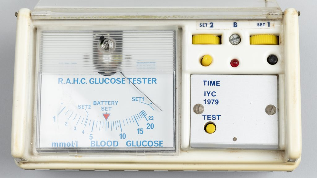 Instrument panel face of R.A.H.C. glucometer. Square shaped gauge with thin black indicator hand on left, yellow operating switches on right.