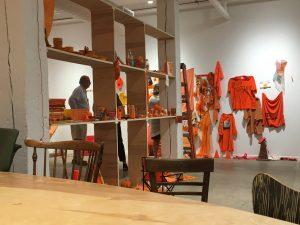Member examines a shelf-like art installation