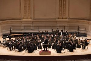 Steven Rash, CAS '05 conducts the Odem HS Wind Ensemble at Carnegie Hall