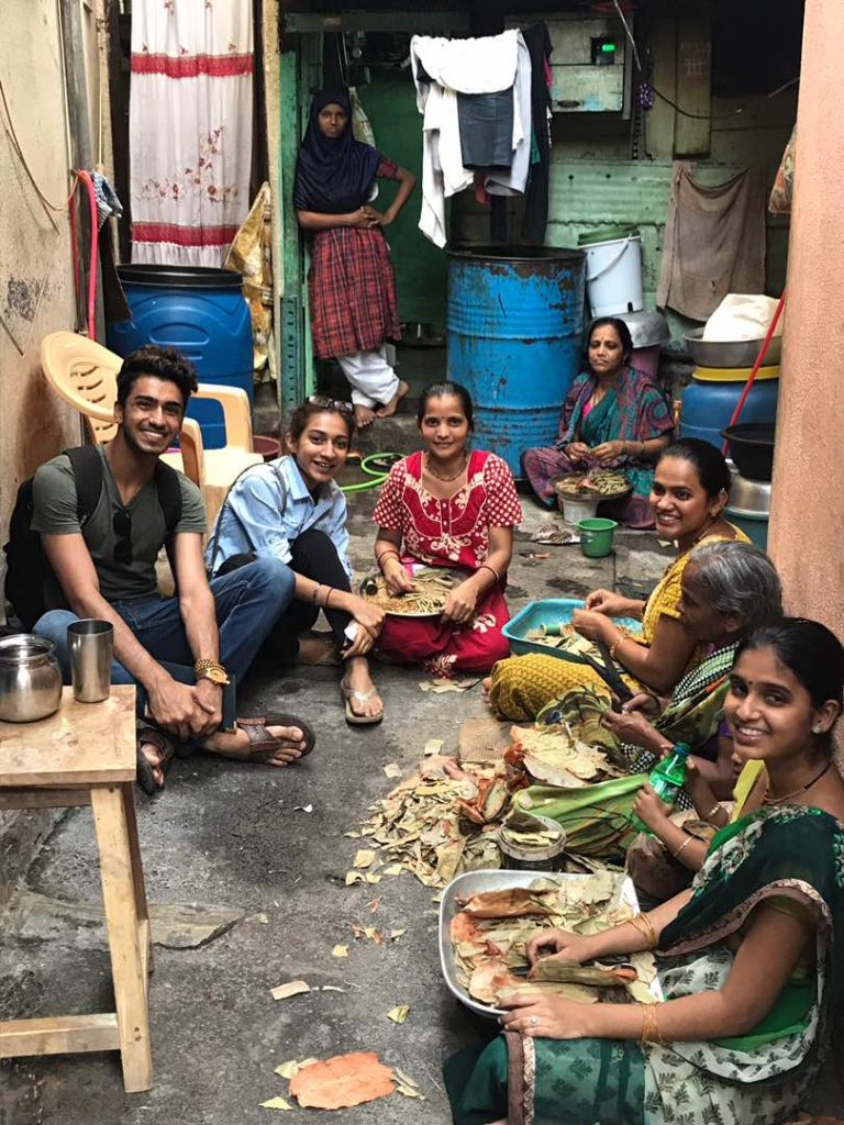 Imshan Dhrolia's research centered around the women who occupy the lowest tier of the tobacco labor industry. Their job includes hand-rolling a popular native cigarette called a bidi. Here Imshan is photographed with a groups of bidi rollers with whom he worked closely for his research.