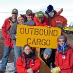 "Eight men and women pose with a sign that says ""Outbound Cargo"" as part of the search for meteorites in Antarctica for the ANSMET  program"
