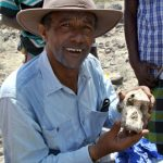 Scientist in Ethiopia wearing broad-rimmed hat and button shirt holds a skull in his hands