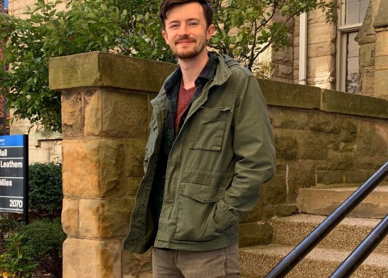 Male student stands on steps and railing near college building