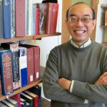 Smiling professor in gray sweater stands with arms crossed in room full of books