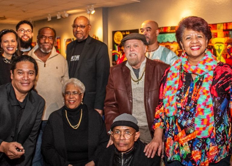 Nine artists and the curator of the African American Alumni Art Exhibition pose for the camera.