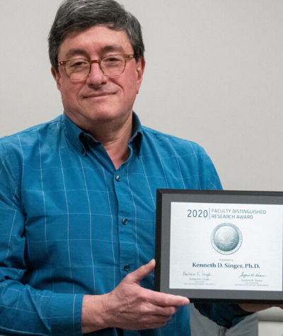 professor in blue shirt and wearing glasses holds award in his hands