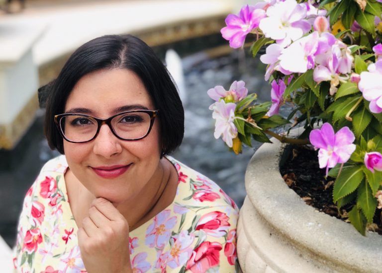 photo of a woman with short brown hair and glasses, smiling with her hand to her chin. She's wearing a floral top and sitting next to a flower planter.