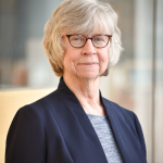 Dean of the College of Arts and Sciences wearing glasses and dark blue blazer